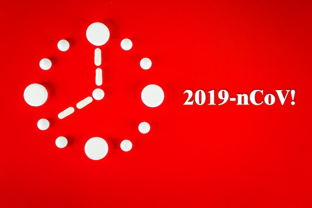 碑文2019-ncov、赤い背景、上面図の白い錠剤で作られた時計。 2019ノベルコロナウイルス2019-ncovコンセプト。