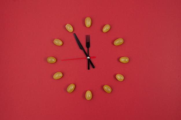 赤い背景に12ピースのブドウの時計。コピースペース付きの新年作曲。