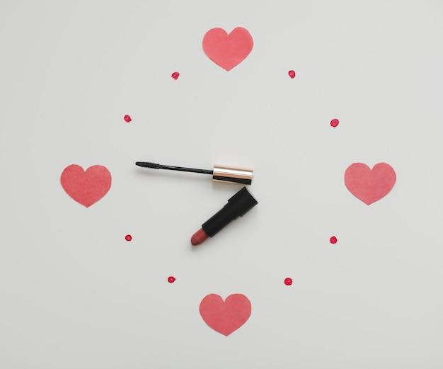Часы на белом фоне из косметических продуктов для макияжа, помады и кисти.