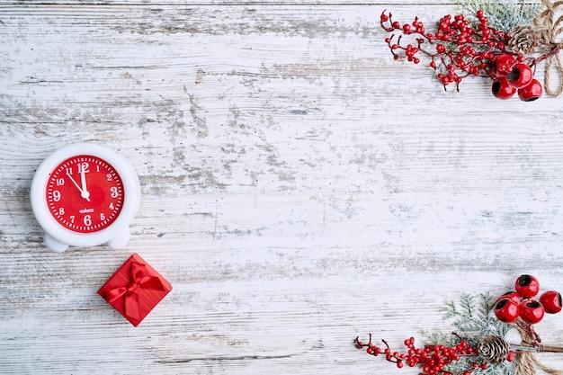 新年またはxmasのための花輪と赤いクリスマスボールで飾られた木製のテーブルの背景に時計。コピースペース