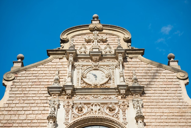 雲のある青い空の上の有名なモントセラトベネディクト修道院の壁の時計。バルセロナ、カタルーニャ、スペイン
