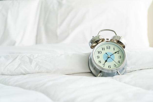 白いベッドの上の時計