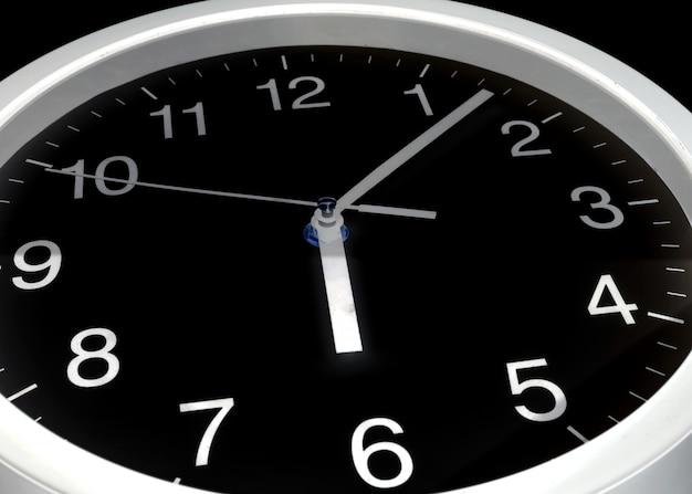 時計または時間の抽象的な背景、黒い時計と白い針、6時、7分