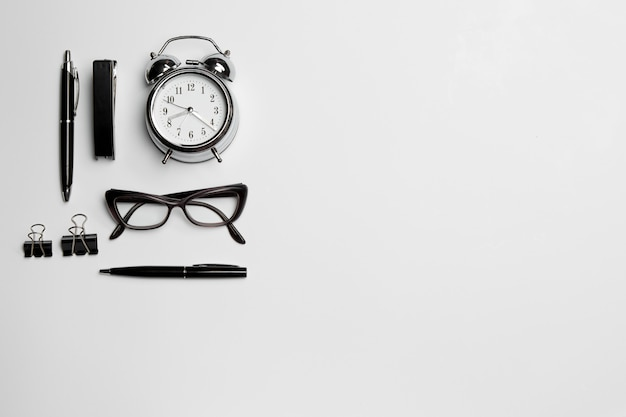Clock, pen, and glasses on white