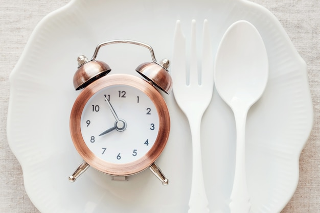 A clock on the plate, intermittent fasting diet concept