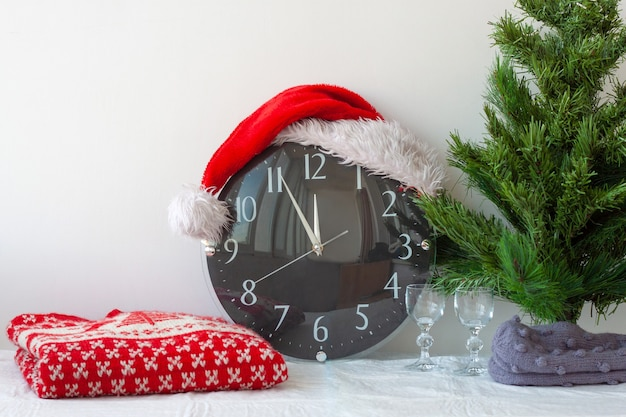 A clock in a santa claus hat next to an artificial christmas tree and a christmas sweater