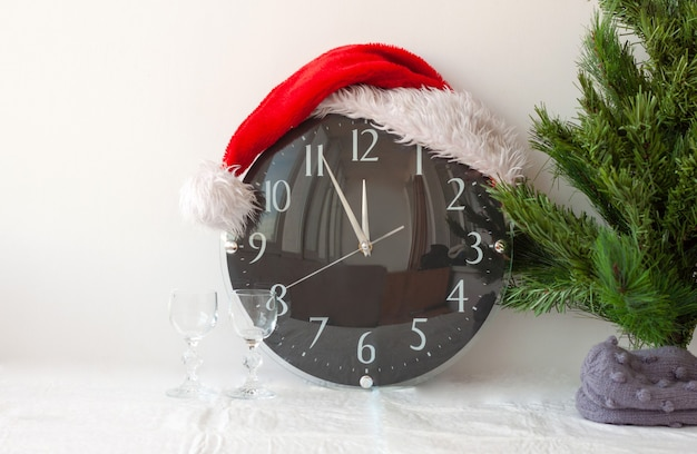 A clock in a santa claus hat next to an artificial christmas tree and two glasses