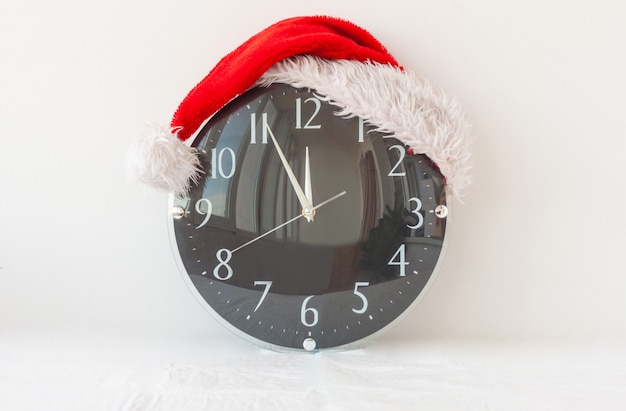 A clock in a santa claus hat on a white background shows five minutes to twelve