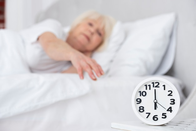 Clock and sleeping elder woman on background