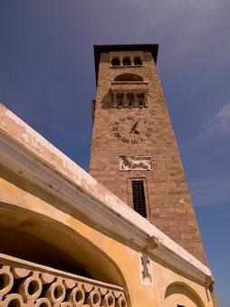 Clock tower at mandraki harbour in rhodes greece