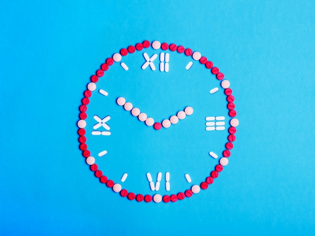 Clock with arrows from medical tablets and pills. health concept