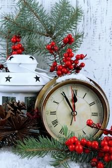 モミの枝と木製の背景のテーブルの上のクリスマスの装飾と時計