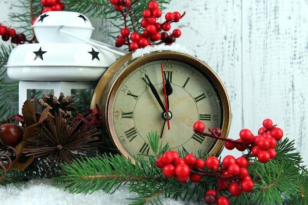 モミの枝とテーブルの上のクリスマスの装飾と時計