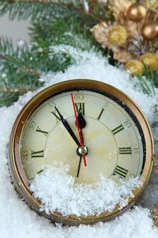 モミの枝と雪の下でクリスマスの装飾がクローズアップ