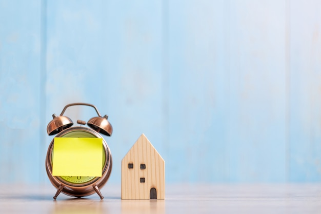 Clock with paper note and house model on wood
