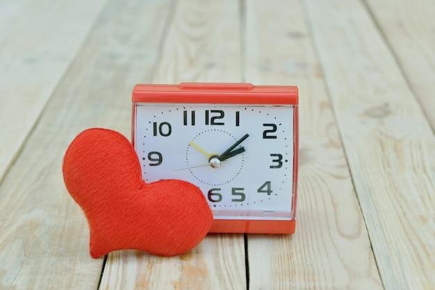 木製の空間に赤いハートの形をした時計。