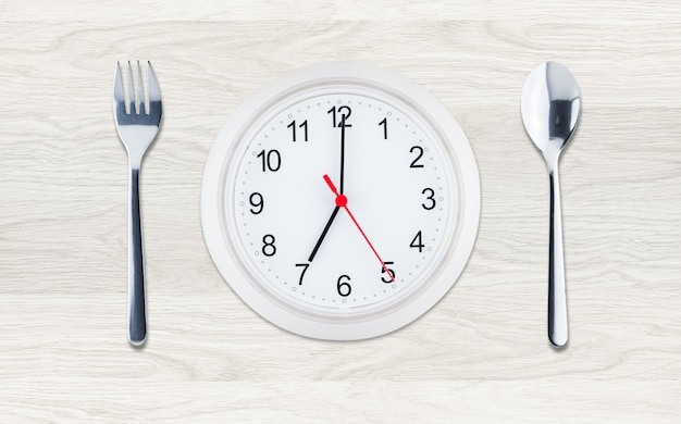 Clock with utensils on clean wood background, flat lay composition