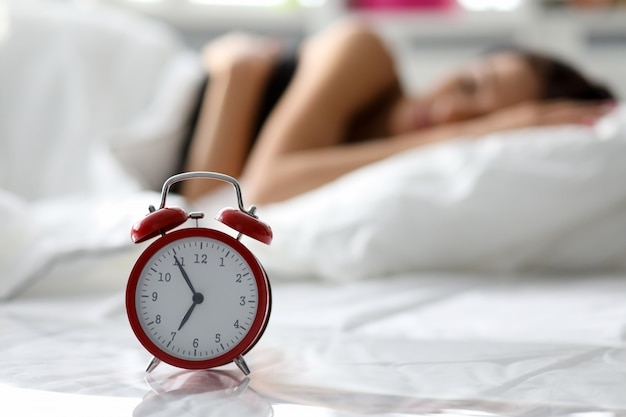 Clock and woman in bed
