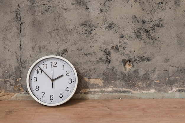 Clock on wooden desk against weathered wall