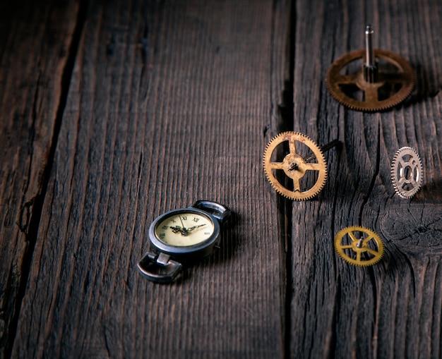 木製のテーブルに時間ブロンズの時計じかけの歯車。コンセプトタイムとアイデアのサポート