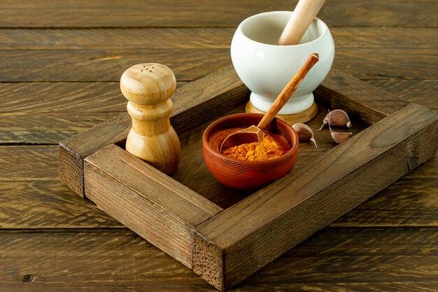 木製の箱のボウルで調理するためのカラフルなさまざまなハーブやスパイスのクロープ。