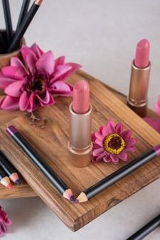 Cloe up photo of brand new lipsticks on wooden board.