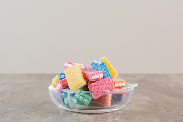 Cloe up photo of homemade colorful candies in bowl over grey.