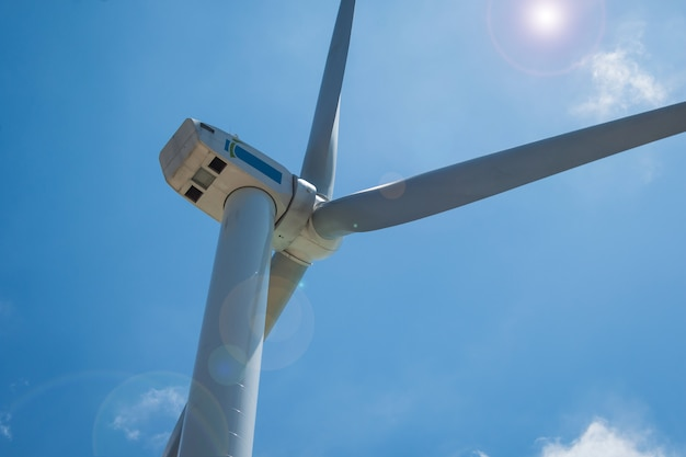 Cloes up wind turbine towers on blue sky background