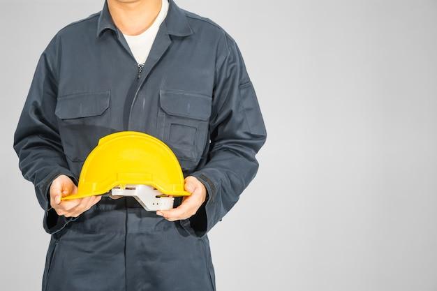Cloes вверх рабочий, стоящий в синем комбинезоне, держащий желтый шлем, изолированный на сером фоне