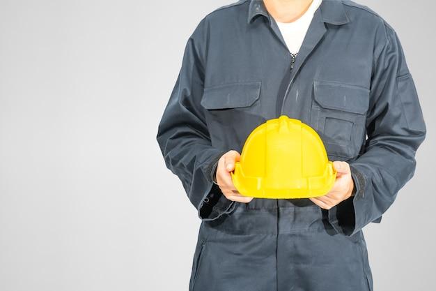 灰色の背景に分離された黄色のヘルメットを保持している青いつなぎ服に立っている労働者を閉じます