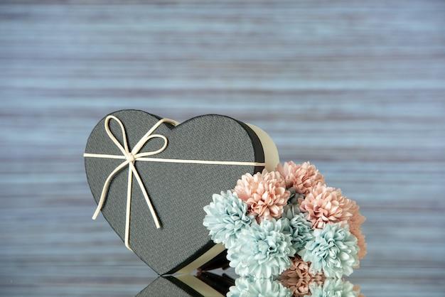 Cloeup vista frontale di fiori colorati scatola a forma di cuore nero