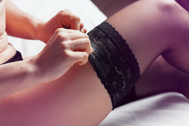 Cloeup portrait of a sexy female body in black lingerie and stockings in bed