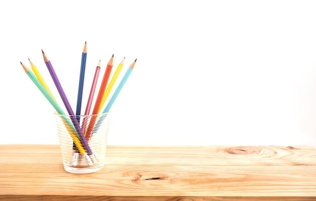나무 막대 테이블 배경에 유리에 clorful 연필