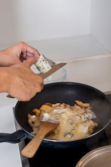 프라이팬에 치즈를 절단하는 사람의 clos-up