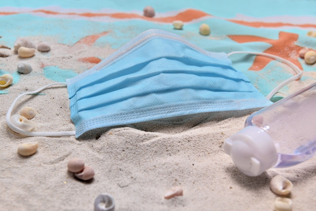 Close to blue surgical mask and hand sanitizer on the beach - concept vacation with covid-19
