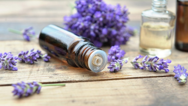 Close on  bottle  of essential oil and bouquet of  lavender flower arranged on a wooden