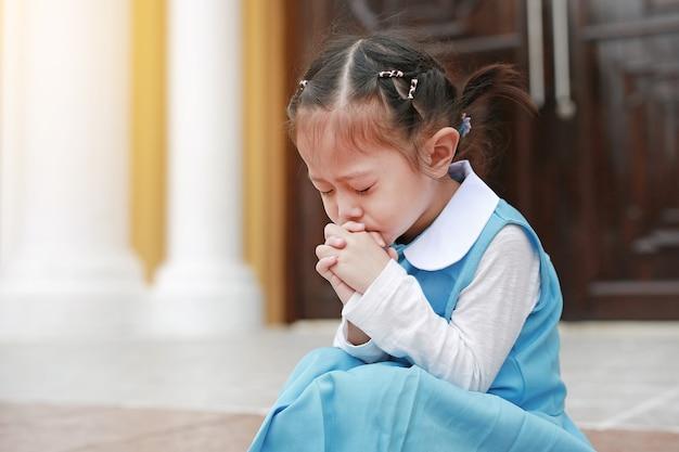 학생 유니폼기도에 눈을 작은 아시아 아이 소녀. 영성과 종교.