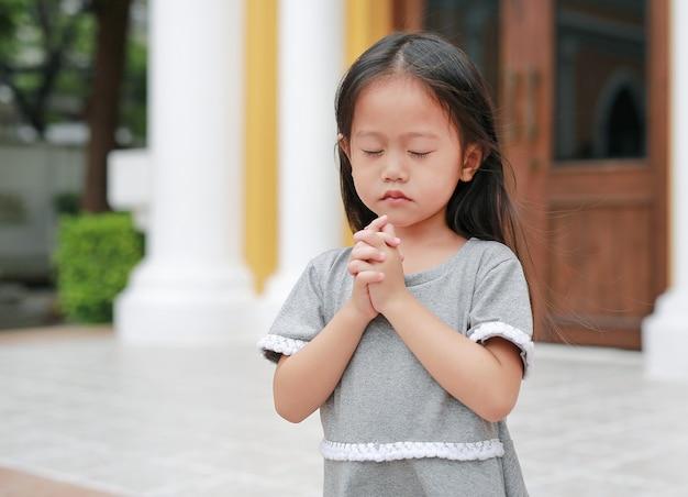 Close eyes little asian girl praying at the church