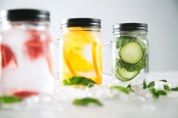 Close focus on last jar healthy fresh cool homemade lemonades with sparkling water strawberry, cucumber, mint and orange isolated in smashed ice cubes on wooden table