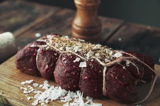 Кусок мяса, перевязанный соленым перцем, готовый к копчению на деревянном столе между травами