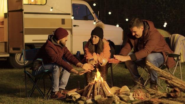 キャンプファイヤーの周りのキャンプチェアに座っている親しい友人が手を温めています。レトロなキャンピングカー。バックグラウンドで電球。