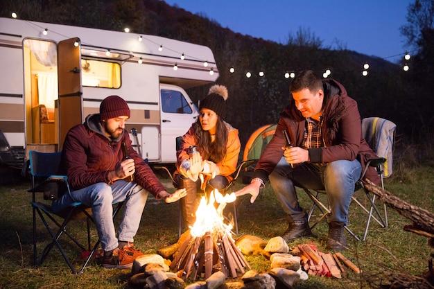 山で一緒にビールを飲み、キャンプファイヤーの周りで手を温めている親しい友人。電球付きのレトロなキャンピングカー。
