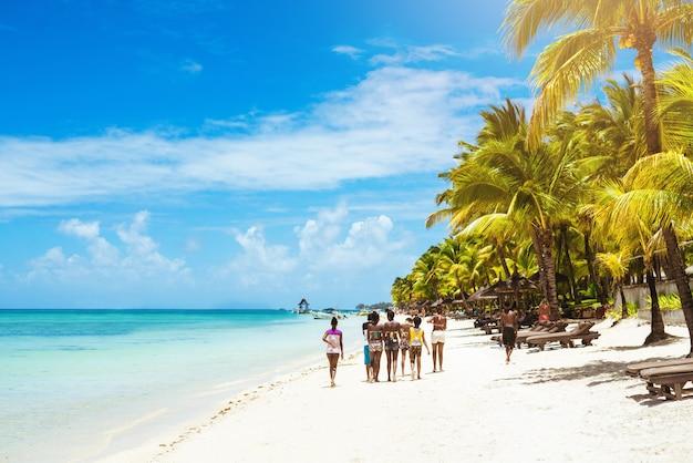 Близкие друзья гуляют по тропическому пляжу в солнечный жаркий день