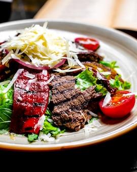 접시에 강판 치즈와 야채와 양상추와 구운 전면 고기를 닫습니다