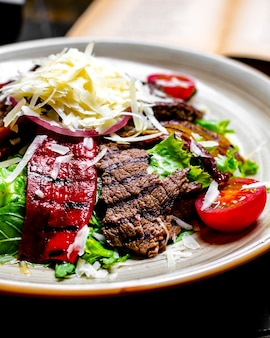 Close front view grilled meat with vegetables and lettuce with grated cheese on a plate