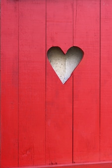 Close on a heart-shaped on a red wooden shutter