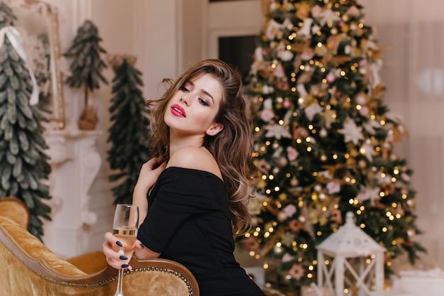 새해 장식에 대한 축제 분위기에서 맛있는 와인을 즐기는 밝은 입술로 유럽 외관의 매력적이고 세련된 여성의 실내 초상화를 닫습니다.