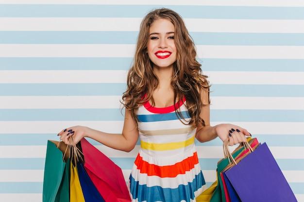 明るいメイクと美しい髪の幸せな女の子の屋内の肖像画を閉じます。ファッショナブルな女の子は、衣料品店の大きな紙袋で買い物やポーズをとるのが大好きです。