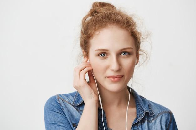 音楽を聴きながらイヤホンを着て、青い目をした優しい豪華な若い赤毛の女の子のクローズアップipの肖像画
