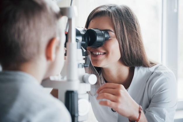 Внимательно смотри. маленький мальчик, проверяющий его глаза с помощью специального оптического аппарата, женщина-врач.